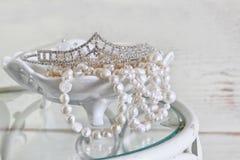 白色的图象成珠状在葡萄酒桌上的项链和金刚石冠状头饰 被过滤的葡萄酒 选择聚焦 库存照片