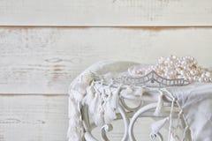 白色的图象成珠状在葡萄酒桌上的项链和金刚石冠状头饰 被过滤的葡萄酒 选择聚焦 免版税库存照片