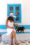 白色的夫人和在一个经典,希腊,蓝色窗口前面的一只猫 免版税库存照片