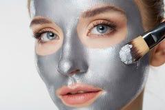 白色的妇女画象护肤健康健康银色面具关闭 免版税库存图片
