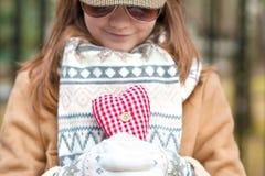 白色的微笑的女孩编织了拿着浪漫红色心脏的手套 免版税库存照片