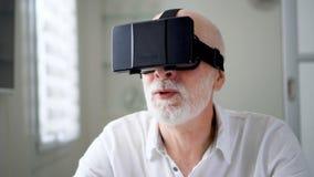 白色的悦目英俊的老人使用VR 360块玻璃在家 活跃现代老年人 股票录像
