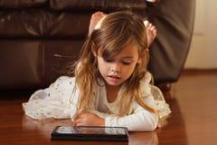 白色的甜四岁的女孩,使用与iPad 免版税图库摄影
