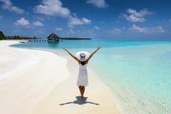 白色的端庄的妇女在一个热带海滩走在马尔代夫 免版税库存图片