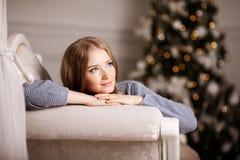 白色的美丽的少妇在圣诞树附近 Beautifu 免版税库存图片