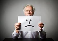 白色的老人拿着与微笑的白皮书 不快乐浓缩 免版税图库摄影