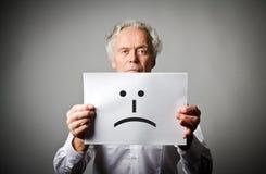 白色的老人拿着与微笑的白皮书 不快乐浓缩 免版税库存照片