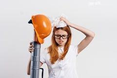 白色的年轻美丽的女性工程师隔绝了背景拿着图纸和安全帽,建筑,设计师 库存图片