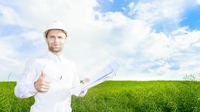 白色盔甲的地质学家在有图画的绿色草甸在手上举行他的赞许 在建造场所的工程师建造者 免版税库存照片