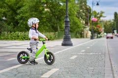 白色盔甲骑马的儿童男孩在他的有盔甲的第一辆自行车 没有脚蹬的自行车 免版税库存图片