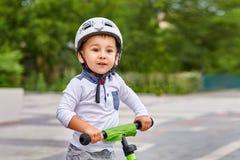 白色盔甲骑马的儿童男孩在他的有盔甲的第一辆自行车 没有脚蹬的自行车 库存图片