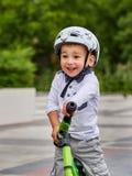 白色盔甲骑马的儿童男孩在他的有盔甲的第一辆自行车 没有脚蹬的自行车 图库摄影
