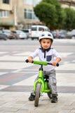 白色盔甲骑马的儿童男孩在他的有盔甲的第一辆自行车 没有脚蹬的自行车 免版税图库摄影