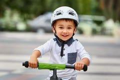 白色盔甲骑马的儿童男孩在他的有盔甲的第一辆自行车 没有脚蹬的自行车 免版税库存照片