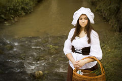 白色盖帽的美妙的中世纪女孩在有篮子的束腰 库存图片