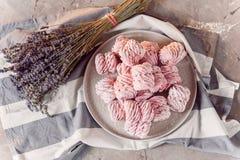 白色盘子用在大理石桌上的新鲜的蛋白软糖与毛巾和淡紫色 免版税库存照片