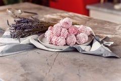 白色盘子用在大理石桌上的新鲜的蛋白软糖与毛巾 库存照片