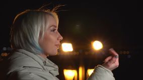 白色盾夹克的少妇邀请来某人 背景的夜城市 股票视频