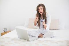 白色睡衣的惊奇偶然棕色毛发的妇女在网上购物与她的膝上型计算机的 图库摄影