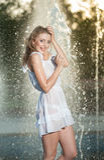 白色短的礼服的可爱的女孩坐栏杆在喷泉附近在夏天最热的天 库存图片