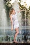 白色短的礼服的可爱的女孩坐栏杆在喷泉附近在夏天最热的天 免版税库存图片