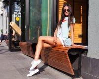 白色短裤的一个美丽的被晒黑的腿长的女孩,一件绿色T恤杉,时兴的白色运动鞋基于一开放夏天咖啡馆benc 图库摄影