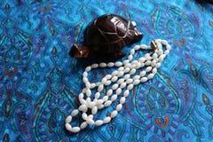 白色石头小珠在棕色木乌龟附近位于 免版税库存图片