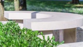 白色石长凳在夏天公园 库存照片