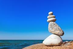 白色石头平衡在蓝天和海背景的  免版税库存图片
