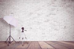 白色砖墙在照片演播室 照明的一把伞和照相机的一个三脚架 空的拷贝空间 库存照片