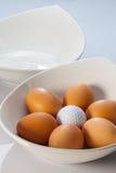 白色碗、复活节彩蛋和高尔夫球 库存图片