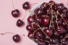 白色碗在桃红色背景的新鲜的红色樱桃 顶视图 特写镜头 免版税图库摄影