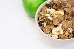 白色碗用黑麦剥落在白色毛巾的muesli用绿色苹果, copyspace,白色背景 免版税库存照片