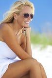 白色礼服和太阳镜的美丽的白肤金发的妇女在海滩 免版税库存照片