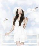 白色礼服和帽子的美丽的深色的妇女 免版税库存图片