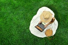 白色礼服和帽子饮用的茶的俏丽的女孩 免版税库存图片