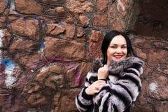 年轻白色礼服和皮大衣的时尚端庄的妇女在b 库存图片
