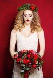 白色礼服和花的美丽的未婚妻在红色 免版税库存照片