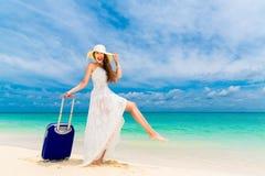 白色礼服和草帽的美丽的少妇带着手提箱 免版税库存照片