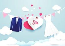白色礼服和蓝色衣服与心脏签署垂悬在云彩天空 免版税库存照片