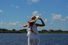 白色礼服和魅力帽子的妇女在河沿 库存照片