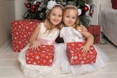白色礼服的两个女孩有礼物的 免版税库存图片