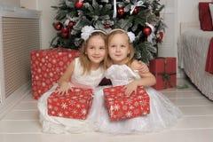 白色礼服的两个女孩有礼物的 库存照片