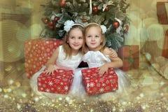 白色礼服的两个女孩有礼物的 图库摄影
