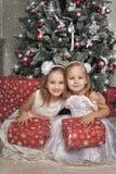 白色礼服的两个女孩有礼物的 免版税库存照片