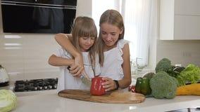 白色礼服的两个逗人喜爱的姐妹在厨房里烹调:女孩切红辣椒做沙拉 更老的姐妹教 股票录像