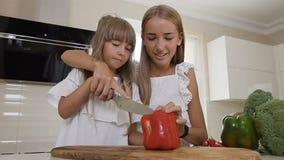 白色礼服的两个青少年的女孩在厨房里烹调:女孩切红辣椒做沙拉 更老的姐妹教 影视素材