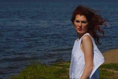 白色礼服的严肃的女孩带着户外严厉的凝视在河岸,在背景的深大海 图库摄影