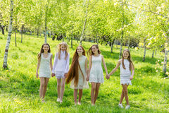 白色礼服的五个美丽的女孩在夏天 免版税库存照片