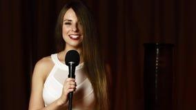 白色礼服的俏丽的女孩拿着话筒并且唱歌与引人入胜的微笑 股票录像